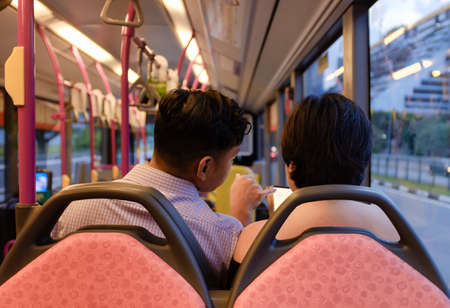 SINGAPORE-08 MAR 2018:couple play smart phone in the bus