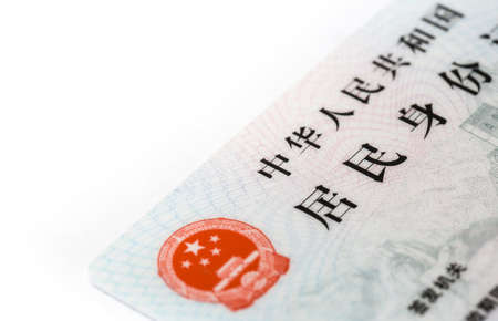 Hand holding card with national emblem of China. Translation: text on top 'People's Republic of China'; text in middle 'Resident Identity Card'; smaller text at bottom 'issued by' and 'expired date'