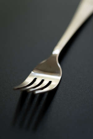 fork on black background. Close-up of stainless fork with copy space. Stock Photo