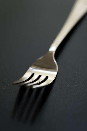 tenedor sobre fondo negro. Primer plano de horquilla de acero inoxidable con espacio de copia. Foto de archivo