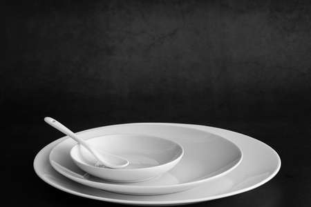 Set of plates with spoon on black table