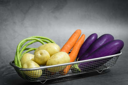 Assorted raw organic vegetables in a metal basket Archivio Fotografico