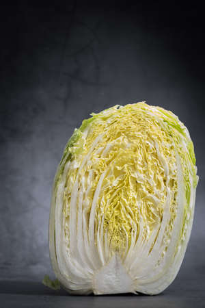 freshly half cut cabbage on black background