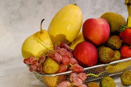Assortment of exotic fruits in metal basket isolated on white
