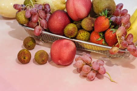 Assortment of exotic fruits in metal basket isolated on light background