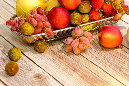 Assortment of exotic fruits in metal basket isolated on wood Archivio Fotografico