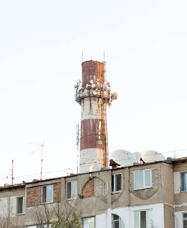 transducer: Brick flue with connected repeaters in an industrial area on the sky background Stock Photo