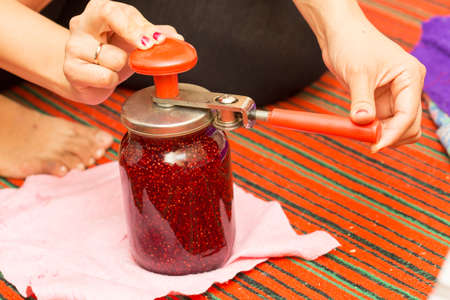hand jam: raspberry jam. Female hand jam. Preparation of delicious raspberry jam in the kitchen. Prepared homemade red raspberry jam over the kitchen. Country style