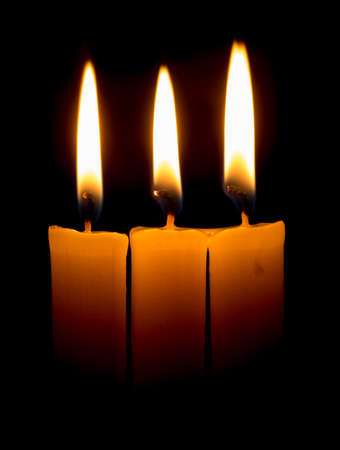 beeswax candle: candle lit brightly against a black background