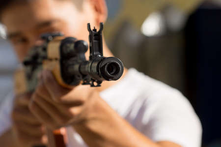 guerrilla warfare: Portrait of a man aiming a gun
