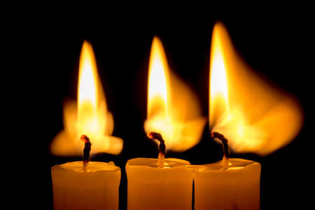 heat loss: candle lit brightly against a black background