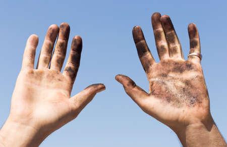 manos sucias: Dirty hands against the blue sky