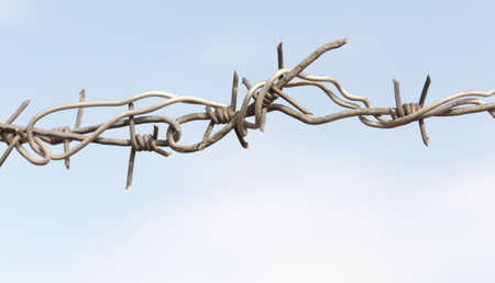 barbed wires against blue sky. Stock Photo