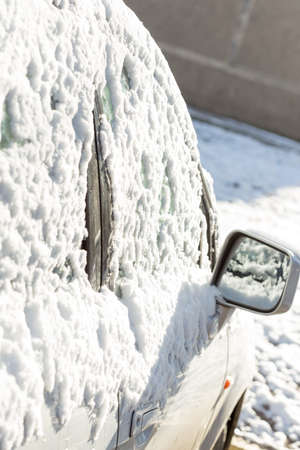 door handle: parked car covered with snow during snowing in winter time Stock Photo