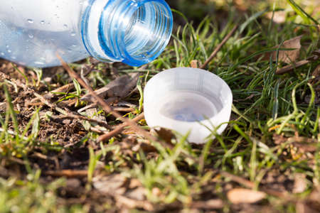 Shredded plastic mineral water bottles and bottle caps on the grass in the park, the concept of environmental protection, environmental protection clogging Stock Photo