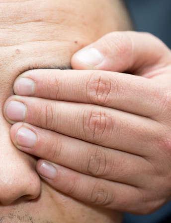 Man closes his eyes with his hand close-up