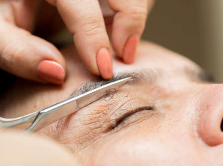 threading hair: care of eyebrows in a beauty salon close-up