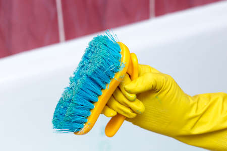 the girl cleans the surface in the bathroom. Girl holding a brush and cleaning her Stock Photo