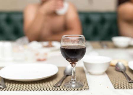 nackter Mann sitzt in der Sauna auf dem Tisch und trinkt Getränke