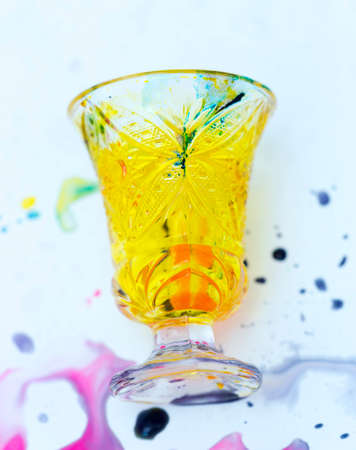 colored paints on a glass beaker Stock Photo