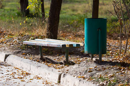 a bench and a trash can in the park