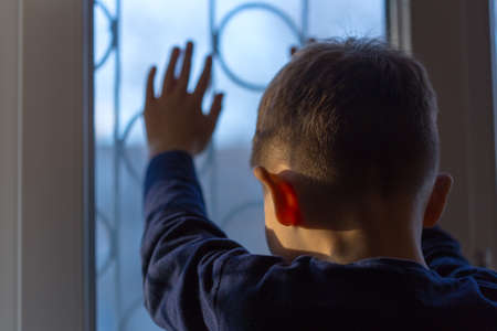 A boy stands and looks out the window at sunset Stock Photo