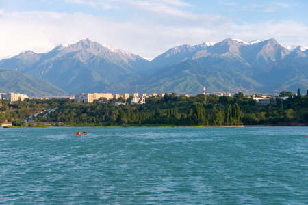 View of the skyscrapers and the mountain at Lake Sairan in the city of Almaty Stock Photo