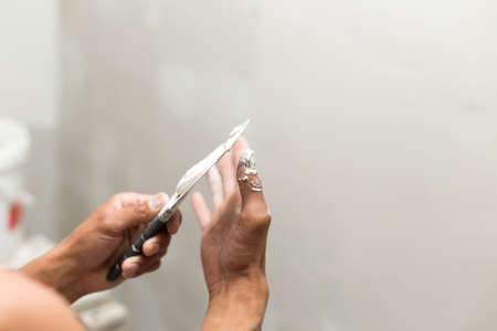 The process of applying the second layer of putty trowel for light plaster walls Фото со стока