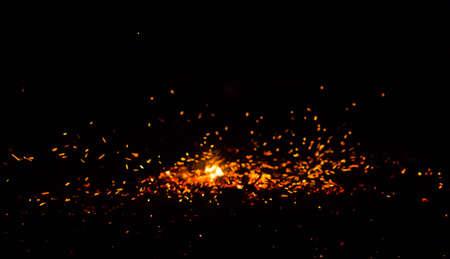 黒い背景に火花を散らす炎