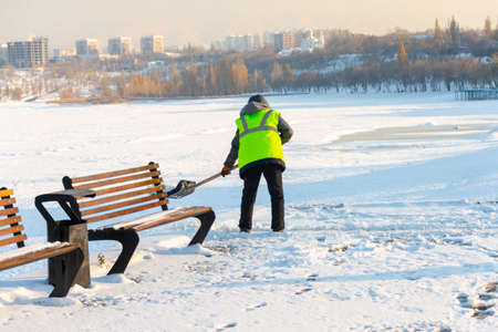 Employees of municipal services in a special form clear the snow from the sidewalk Stock Photo