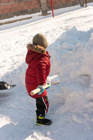 boy cleans snow in the yard