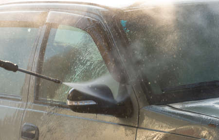 Spraying water from a high pressure hose to the side of a car at a self-service car wash Imagens