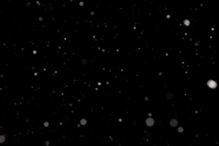 Snowstorm texture. Bokeh lights on black background, shot of flying snowflakes in the air 스톡 콘텐츠