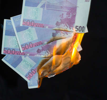 five hundred euro fakes are burning on a black background