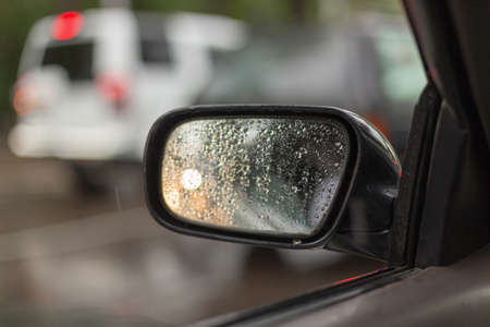 Car side mirror glass with water droplets from rain - driver's side rear view on rainy day