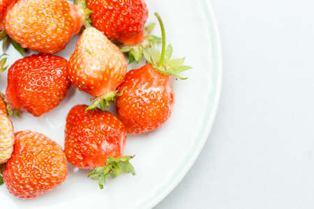 Strawberries on a white background, fresh, tasty and natural strawberries from grandfather's garden on a white plate
