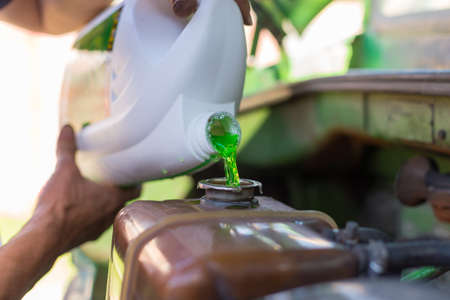 Male hands holding a bottle of green antifreeze. The liquid is poured into the throat at MI temperatures, self-replacement at home