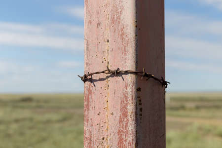 barbed wire on an iron rack against the blue sky