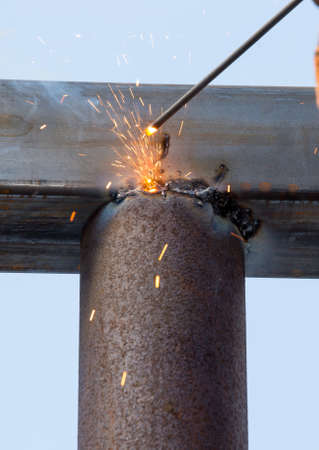 close-up of arc welding in the workplace, fastening the steel canopy frame with protective helmets from flying sparks. Gloves in hand