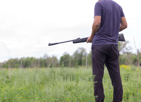Young man shoots air rifle in nature Stock Photo