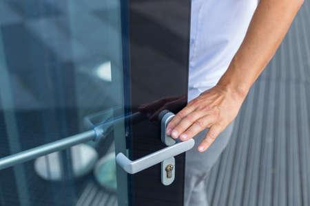 Mano dell'uomo che si prepara ad aprire la porta per entrare in ufficio Archivio Fotografico