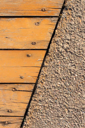 wood texture is painted yellow with paints and seams with concrete walls