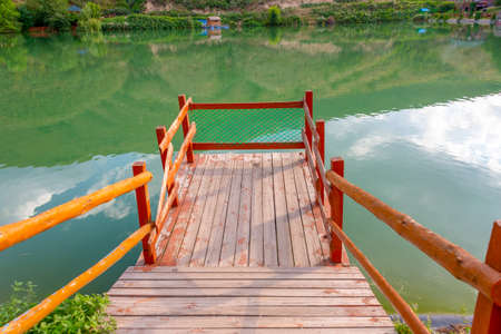 Autumn paradise. Wooden ladder for fishing in the river. Green water in the lake