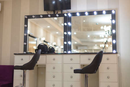 Decorative cosmetics and dressing table near the mirror in the dressing room