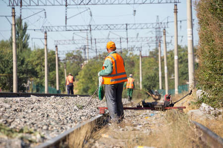 workers check for broken old reinforced concrete sleepers to replace them with new ones on the railway using equipment