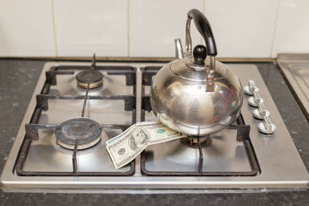 one hundred dollar bills on a gas stove under the kettle, gas is not burning.