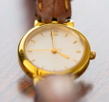 womens gold watch with a leather strap on the table, close-up