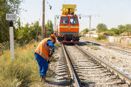 workers replace old wires with new ones in the railway using equipment