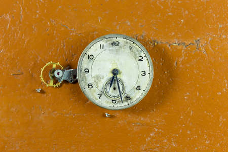 mechanical clock on the table, yellow background Standard-Bild