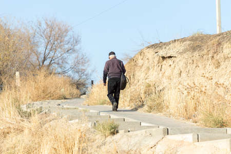 a gray-haired old man climbs the stairs. Senior healthy lifestyle.